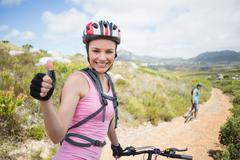Stock Photo of Fit couple cycling on mountain trail woman smiling at camera
