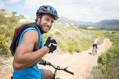 Stock Photo of Fit couple cycling on mountain trail man smiling at camera