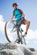 Stock Photo of Fit man cycling on rocky terrain