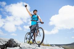 Fit man cycling on rocky terrain and cheering - stock photo