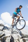 Fit man cycling on rocky terrain - stock photo