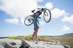 Fit man walking on rocky terrain holding mountain bike - stock photo