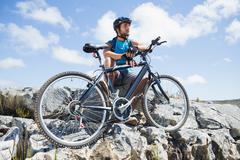 Fit cyclist taking a break on rocky peak - stock photo