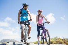 Fit cyclist couple taking a break on rocky peak smiling at each other - stock photo
