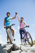 Fit cyclist couple happy to have reached the summit - stock photo