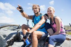 Fit cyclist couple taking a break on rocky peak Stock Photos