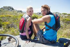 Fit cyclist couple taking a break on rocky peak smiling at camera - stock photo