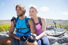 Fit cyclist couple taking a break on rocky peak - stock photo