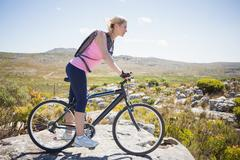 Fit pretty cyclist on a rocky terrain - stock photo