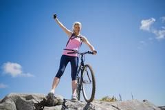 Fit pretty cyclist on a rocky terrain smiling at camera - stock photo