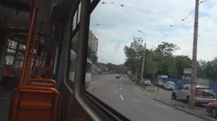 Steady shot inside moving tram cars driving beside tramcar stopping at red light Stock Footage