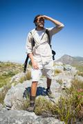 Stock Photo of Handsome hiker standing at the summit looking around