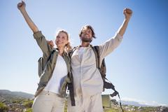 Stock Photo of Hiking couple standing on mountain terrain cheering