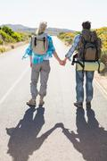 Stock Photo of Attractive couple standing on the road holding hands