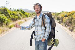 Stock Photo of Attractive man hitch hiking on rural road