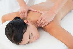 Beautiful brunette enjoying a back massage Kuvituskuvat