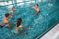 Fitness class doing aqua aerobics on exercise bikes Stock Photos
