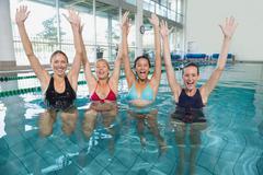 Stock Photo of Female fitness class doing aqua aerobics and cheering