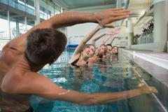 Female fitness class doing aqua aerobics with male instructor - stock photo