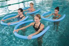 Fitness class doing aqua aerobics with foam rollers Stock Photos