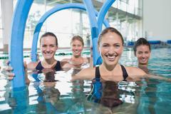 Female fitness class doing aqua aerobics with foam rollers Stock Photos