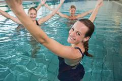 Stock Photo of Smiling female fitness class doing aqua aerobics