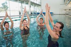 Stock Photo of Smiling female fitness class doing aqua aerobics