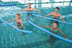 Stock Photo of Happy fitness class doing aqua aerobics with foam rollers