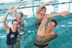 Stock Photo of Happy fitness class doing aqua aerobics