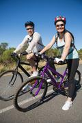 Active happy couple going for a bike ride in the countryside - stock photo