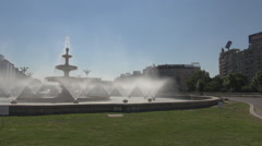 Green grass, beautiful huge water fountain, car traffic around square, cityscape Stock Footage