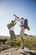 Hiking couple jumping and cheering on rocky terrain - stock photo