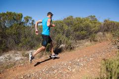 Athletic man jogging up country trail Stock Photos