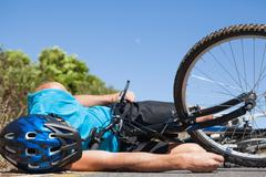 Cyclist lying on the road after an accident Stock Photos