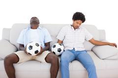 Distraught football fans sitting on the couch with balls Stock Photos