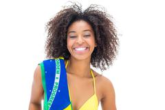 Stock Photo of Fit girl in yellow bikini holding brazil flag smiling at camera
