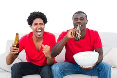 Football fans in red cheering on the sofa with beers and popcorn Stock Photos