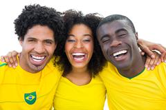 Happy brazilian football fans in yellow smiling at camera Stock Photos