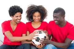 Football fans in red holding ball together - stock photo