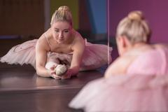 Graceful ballerina warming up in front of mirror - stock photo