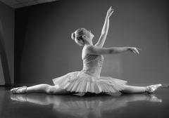 Graceful ballerina sitting with legs stretched out - stock photo