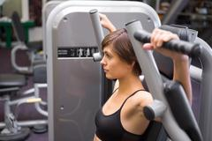 Athletic brunette using weights machine for arms - stock photo