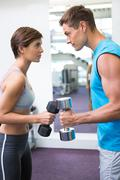 Fit couple lifting dumbbells together facing off - stock photo