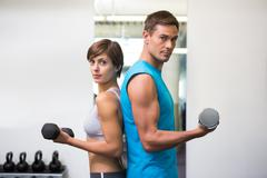 Stock Photo of Fit couple lifting dumbbells together