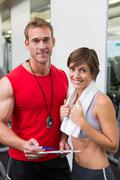 Stock Photo of Handsome personal trainer with his client smiling at camera