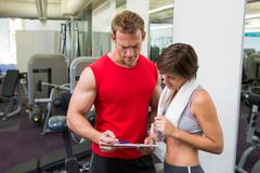 Handsome personal trainer with his client looking at clipboard - stock photo
