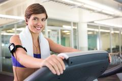 Fit brunette running on the treadmill listening to music - stock photo