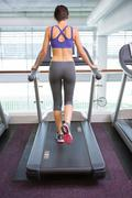 Fit woman running on the treadmill - stock photo