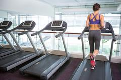 Fit brunette running on the treadmill - stock photo