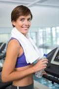 Fit brunette smiling at camera on the treadmill Stock Photos